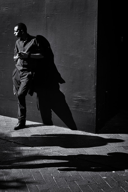 A man leans against a wall casting a shadow while the shadows of two other people pass before him