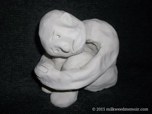 Naive statue of sad an sitting, arms wrapped around knees, head on knees, los fresnos, Texas