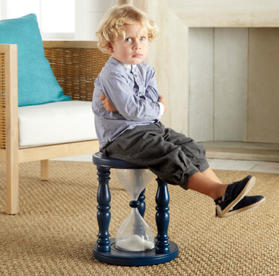child sitting on hourglass timer stool