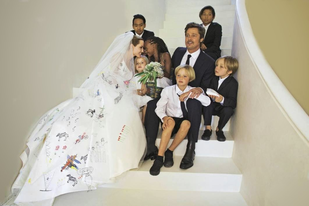 Angelina Jolie, 39, and Brad Pitt, 50, have finally shared photos from their secret wedding! Angelina is every bit the stunning bride, especially with her one-of-a-kind wedding dress!. Brangelina tied the knot in the chapel of Château Miraval, the couple's estate in France on Aug. 23, and now we're getting a glimpse at the big day. Angelina wore a breathtakingly unique dress, as seen on the covers of People and Hello! Instead of a normal wedding gown, she let her kids have a part in styling her dress. what do you think of Angelina and Brad's wedding photos? Do you love her wedding dress? Let us know!.