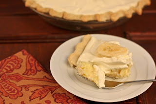 bite of banana cream pie next to slice on white plate