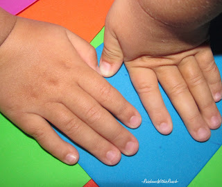 child's hands against color, shapes