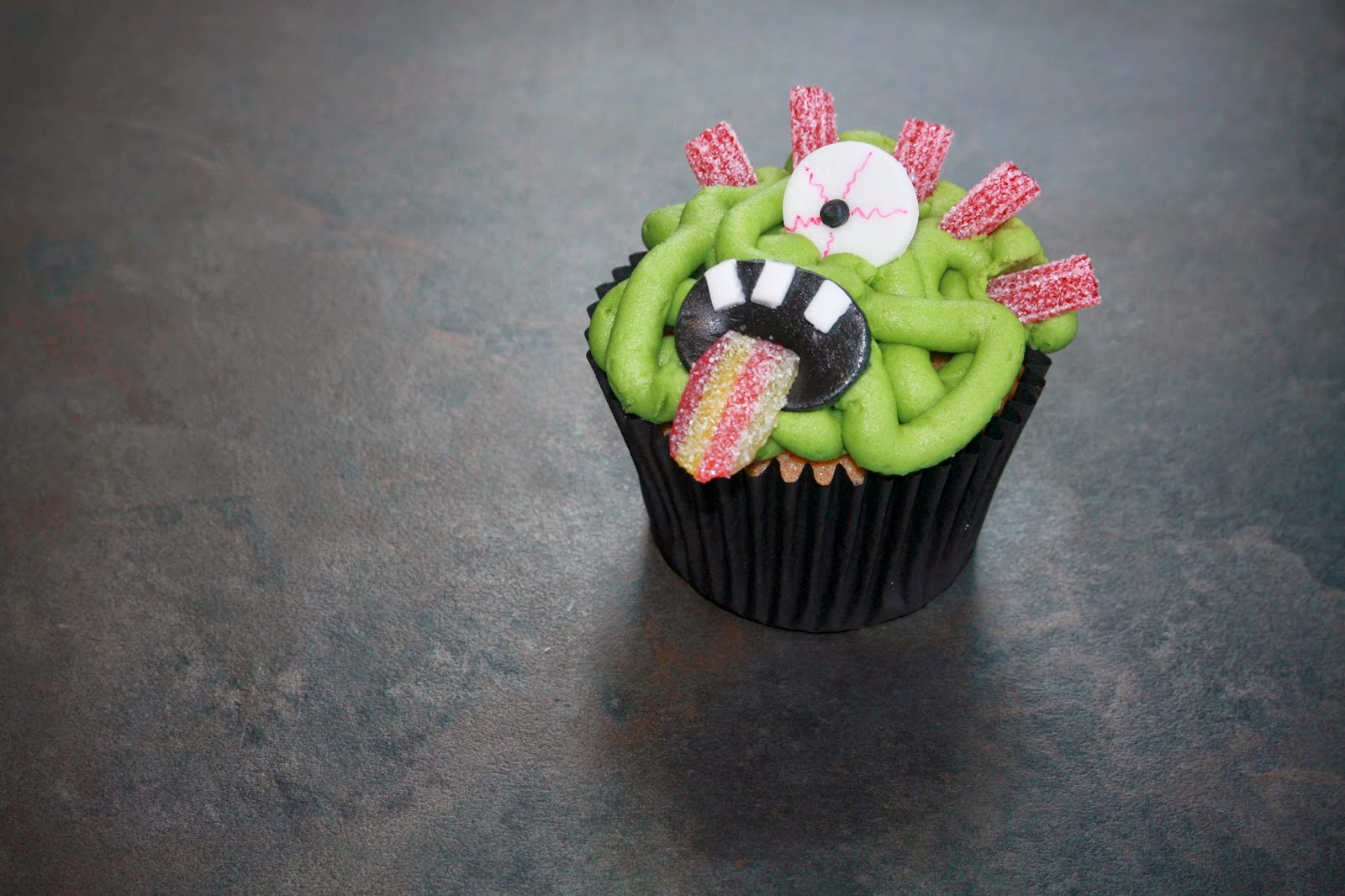 Green monster cupcake sticking out his multi-coloured tongue!