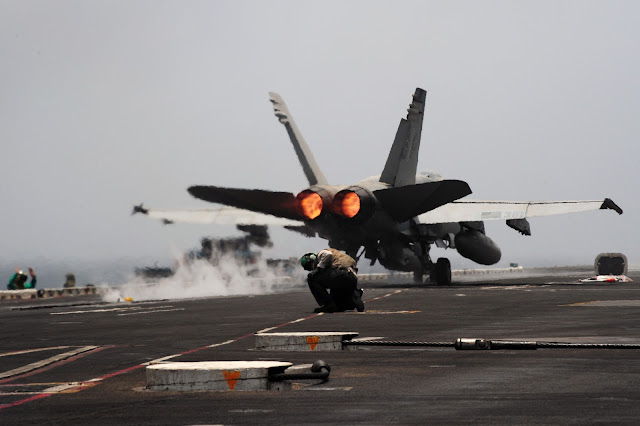 An F/A-18C Hornet from the Rampagers of Strike Fighter Squadron (VFA) 83 launches from the flight deck with full afterburners