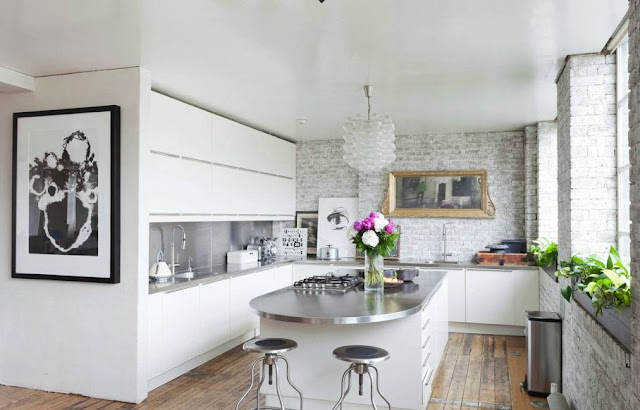 kitchen with exposed brick, sleek white cabinets and an island with metal countertop and white drawers with long pull