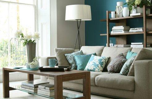 Decoração de sala pequena com sofá de três lugares cinza em tons  de azul claro.