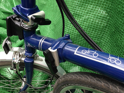 Blue Brompton folding bike showing newer machine brazed main hinge