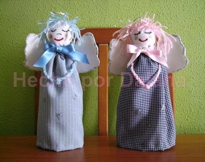 Dos ángeles creados con cartón y tela que estánd e pie sobre una mesa