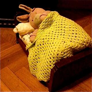 NIñas juegan con sus muñecos envueltos con las mantas de abuela hechas a ganchillo