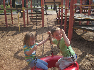 Two children on a tyre swing at a playground