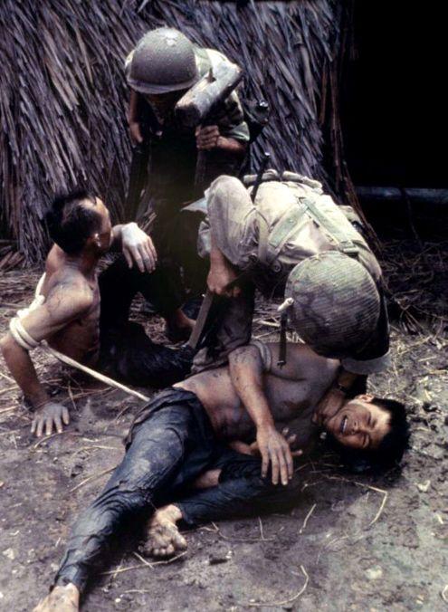 American soldiers interrogate Vietnamese villagers