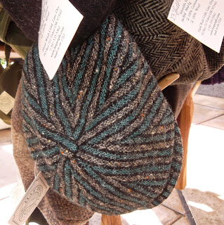 Hats hanging from pegs on a pole. In the foreground is the eight-paneled crown of a hat with stripes of gray, charcoal and teal twill