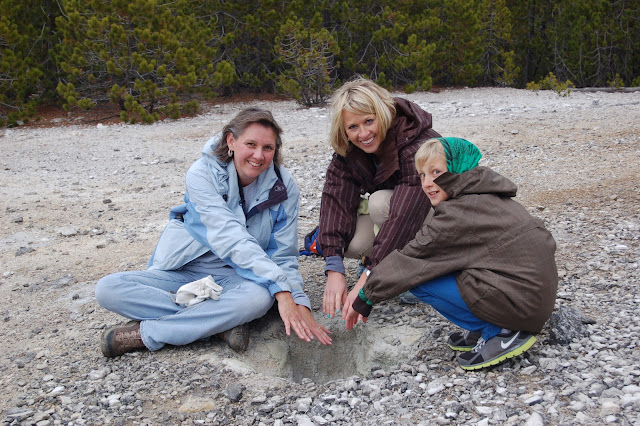 Callie, Gavin, and Kaye warming their hands on a steam vent in Yellowstone