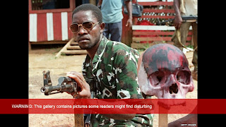 A rebel loyal to Charles Taylor holding Kalashnikov poses next to a painted scull of a Krahn ethnic soldier of president Samuel Doe, 15 May 1990 in Monrovia.