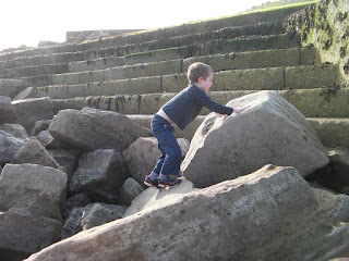 climbing large tidal defence rock formation on seashore southsea seafront