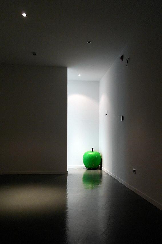 Foto de uma sala vazia com uma maçã gigante a um canto, bem iluminada e o resto, tudo em penumbra
