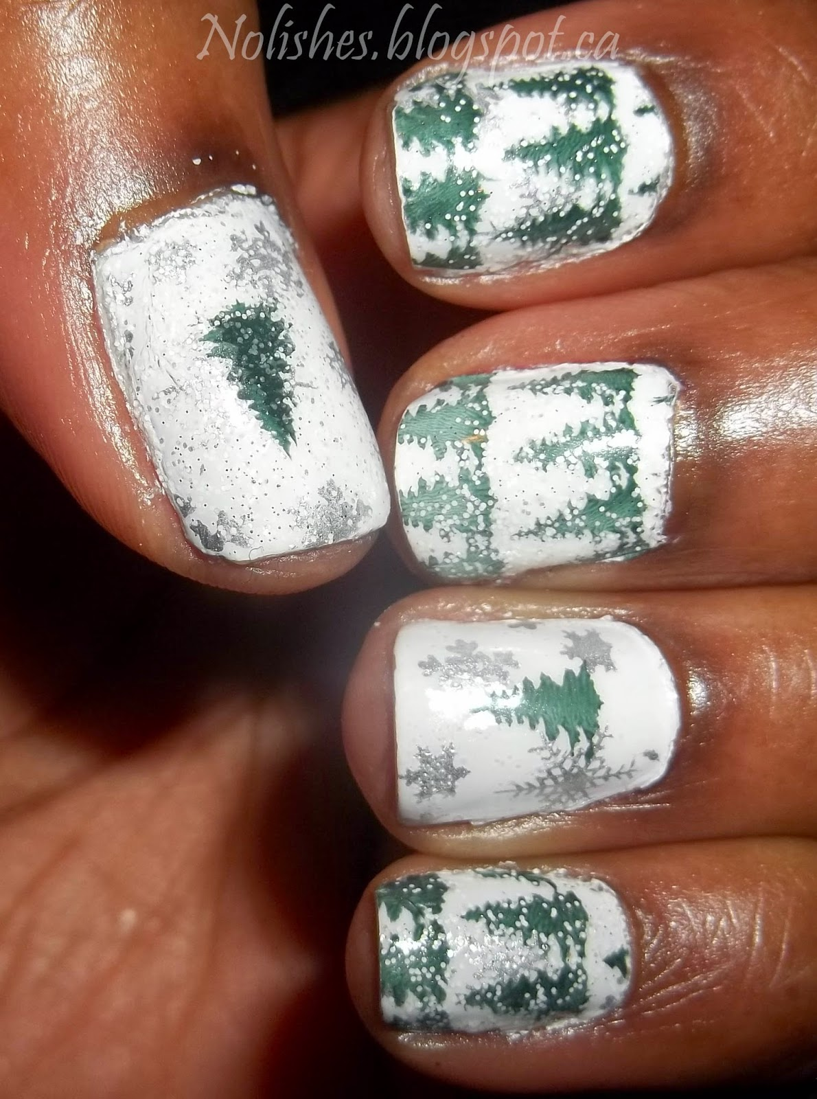nail stamping manicure featuring forest green pine trees over white background with silver snowflakes - left hand
