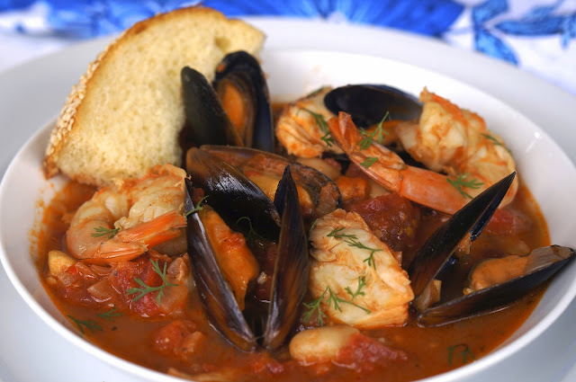 spicy fish stew, fire roasted tomatoes, garlic, crushed red pepper, cilantro, lemon peel, halibut, shrimp, gantry bay seafood mussels in a garlic butter sauce