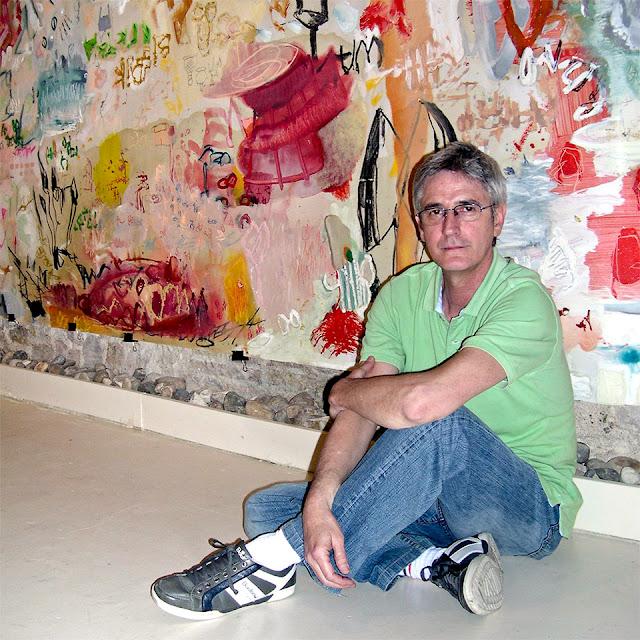 El autor delante de un mural enrollable obra suya