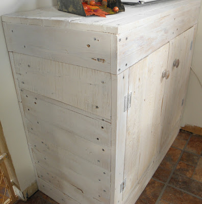 white washed storage cabinet made from an old pallet