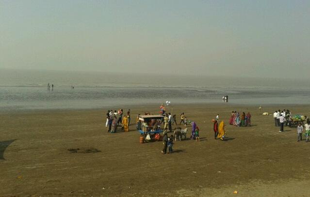 Tourists enjoying the evening in Dumas Beach