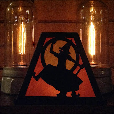 Classic orange and black silhouette of dancing cursing witch paper decoration with retro-style bulb fixtures in background