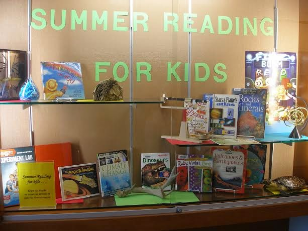 Arrangement of books and scientific instruments inside a glass case. Large green cut-out letters spell: 'Summer Reading for Kids.' On a shelf at right, a poster proclaims this year's summer reading theme, 'Fizz Boom Read.'