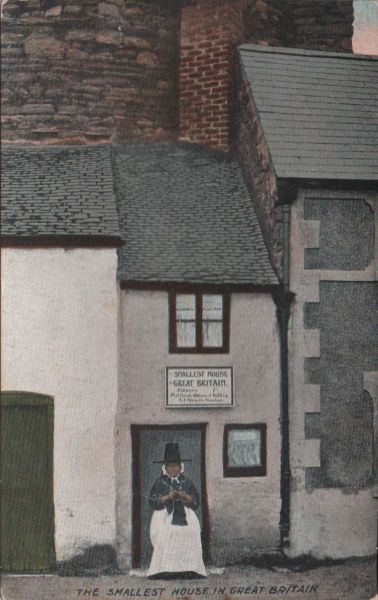 vintage postcard of a tiny terraced house, woman in Welsh costume