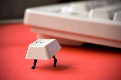 esc key with little black legs sneaking away
