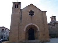 La façana de ponent amb la portalada romànica, la rosassa i la torre que permet pujar a la teulada. A la dreta de la imatge es veu l'església nova