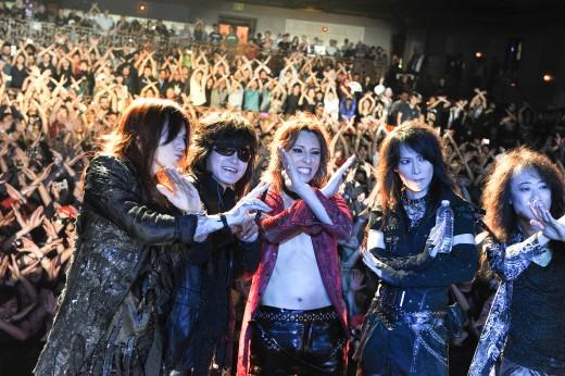ライブ後にステージ上で観客とXポーズをしているX JAPANの画像