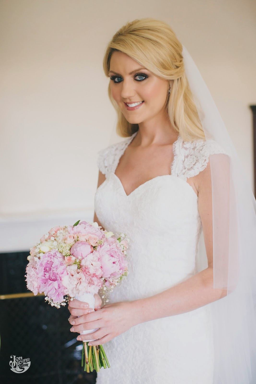 Blonde bride with loose flowing waves wearing her lace embellished gown with veil.