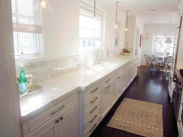 galley kitchen with marble countertops, white cabinets, pendent lights, raised panel polished nickel hardware and dark wood floors