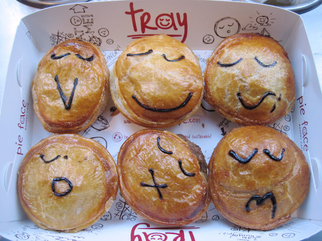 A full tray of meat pies with unique faces artfully displayed by the artists of Pie Face a new in new york restaurant