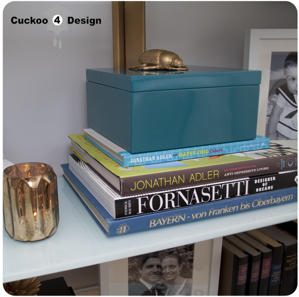 brass and mint glass bookshelf