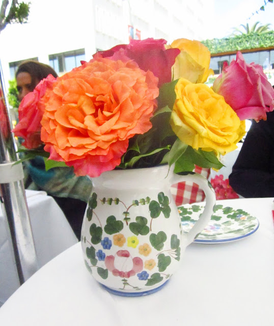 flower arrangement with orange, yellow and pink roses in a white pitcher with flowers on it