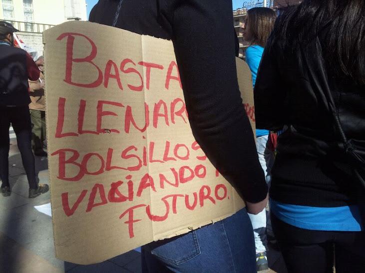 un joven con una pancarta de protesta bajo el brazo