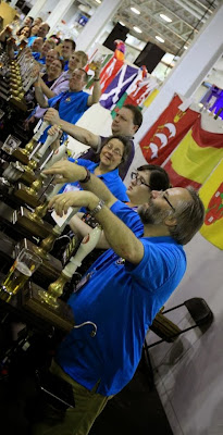 Row of blue shirted people working behind a CAMRA bar - leaning on handpumps