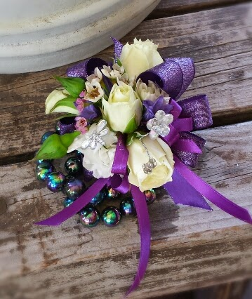 Purple ribbons and white roses, rose buds, wax flower and stock blooms.