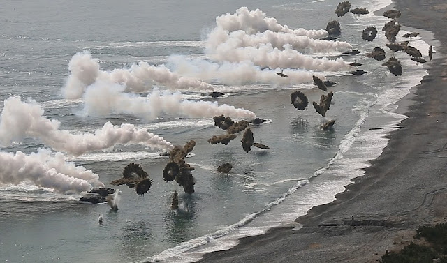 Republic of Korea and U.S. Marine amphibious assault vehicles deploy smoke grenades before storming the shoreline during the amphibious assault portion of exercise Ssang Yong 2014 at Dokseok-ri Beach in Pohang, ROK March 31. Ssang Yong exercises the amphibious capabilities of the ROK-U.S. Navy and Marine Corps team and is a tribute to the maturity of ROK-U.S. relationship. For the exercise, both the ROK and U.S. AAVs were commanded by the 3rd Marine Expeditionary Brigade, III Marine Expeditionary Force. (U.S. Marine Corps photo by Cpl. Matthew Manning/Released)