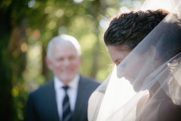 natural photograph captures bride smiling while father looks on