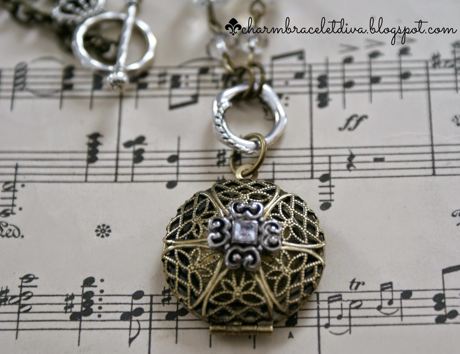 filigree antique brass locket with repurposed charm and faceted beads