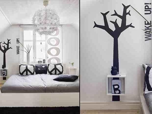 Grafika na ścianach, grafika na poduszkach, czarne drzewo na białej ścianie, białe wnętrze, skandynawski styl wew wnętrzach