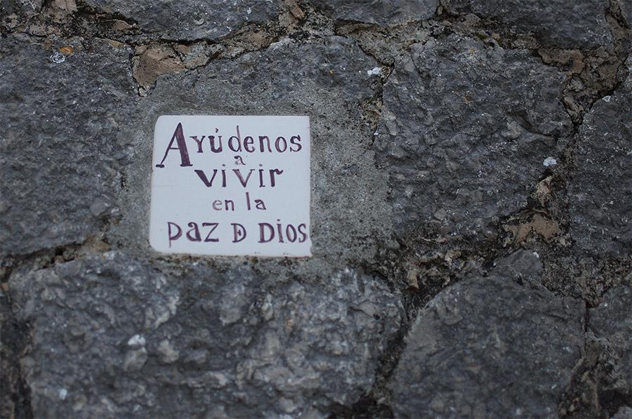 Azulejo en pared de piedra en la ermita de Valldemossa en el que reza la frase: Ayudenos a vivir en la paz de Dios