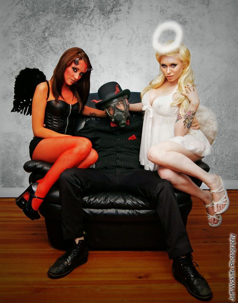 photo de cosplay sexy d'un homme en masque à gaz assis sur un fauteuil avec sa démone et son ange gardien