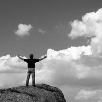homem-topo-montanha-nuvens-céu-braços-abertos