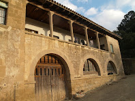 Detall del portal, les finestres d'arc i la porxada amb pilars del cos adossat