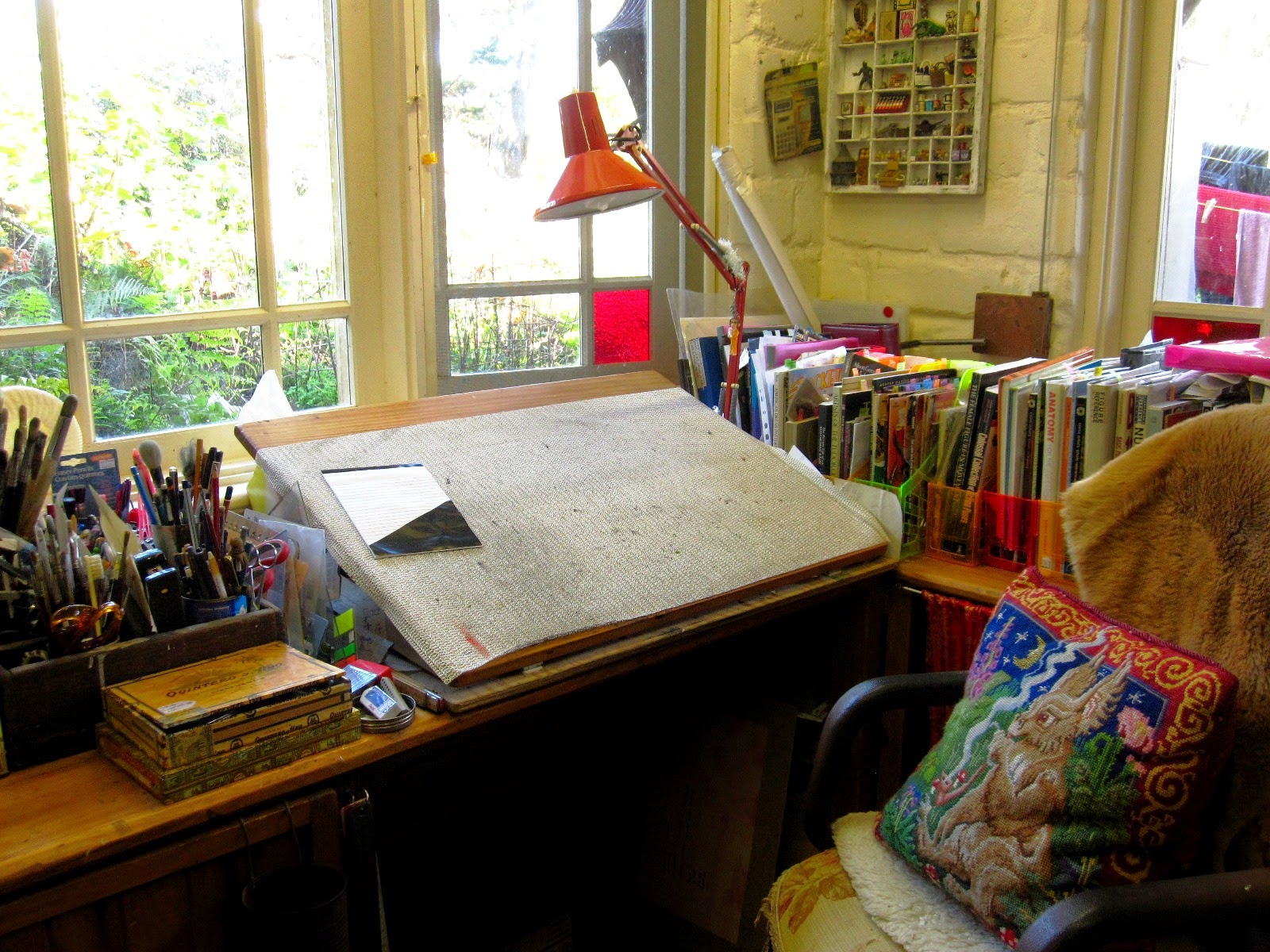 Drawing table with lamp, in the corner of a room overlooking the garden. On the desk chair is a tapestry cushion of a fantasy creature.