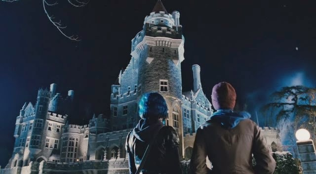 Night scene. A young couple (male and female) are standing side by side looking at the castle (Casa Loma).