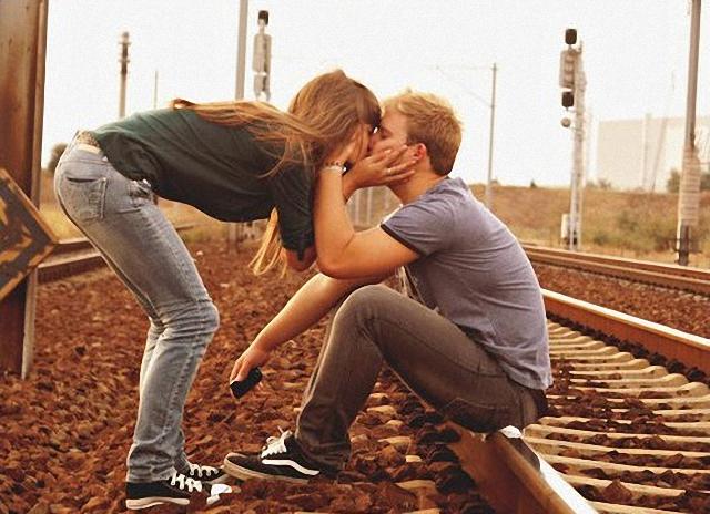Beso al lado de los rieles del tren.